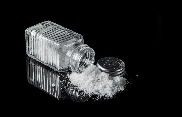 검은 배경에 소금 통에서 소금 힙. 당뇨병이나 다른 질병의 원인이 될 수 있는 과도한 염분 섭취의 개념. 무료 광고 공간