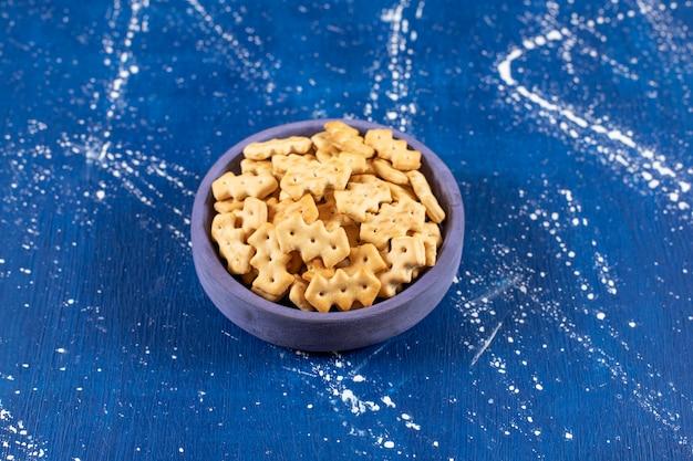 青いボウルに置かれた塩辛い小さなクラッカーのヒープ