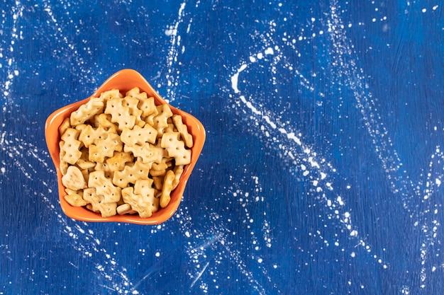 オレンジボウルに入れられた塩辛い小さなクラッカーの山。