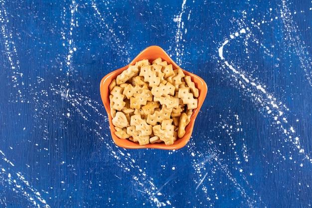 オレンジボウルに入れられた塩辛い小さなクラッカーの山