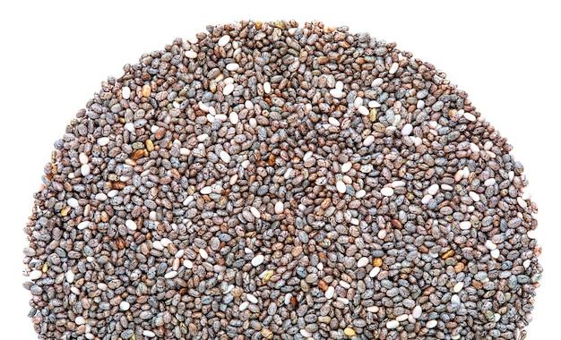 Куча семян чиа сермициркулярной формы вид сверху макро крупным планом с копией пространства