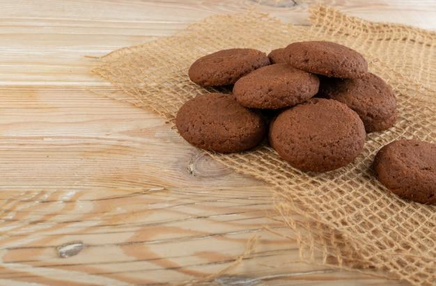 素朴なテーブルの背景にチョコレートが詰まった柔らかい自家製チョコレートバタークッキーのヒープ。