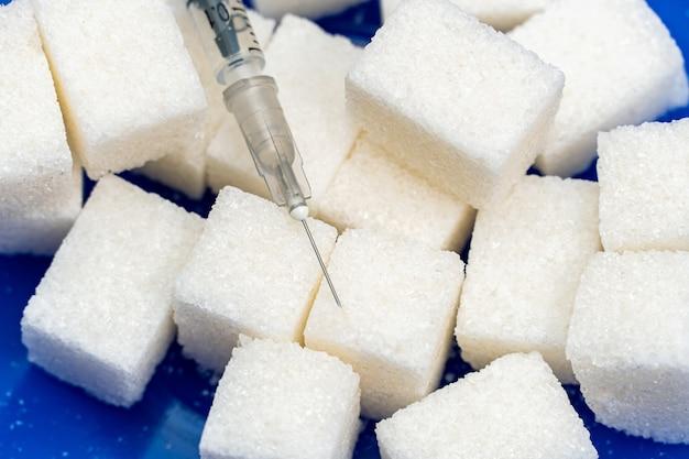 Куча сахара и шприц на синем фоне. тестирование, концепция лечения диабета