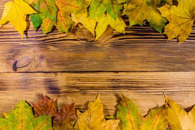 黄色いカエデの葉の山が木製のテーブルに。上面図