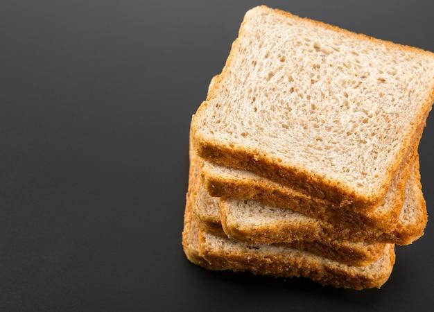 Куча поджаренных ломтиков хлеба на завтрак, изолированные на сером фоне студии.