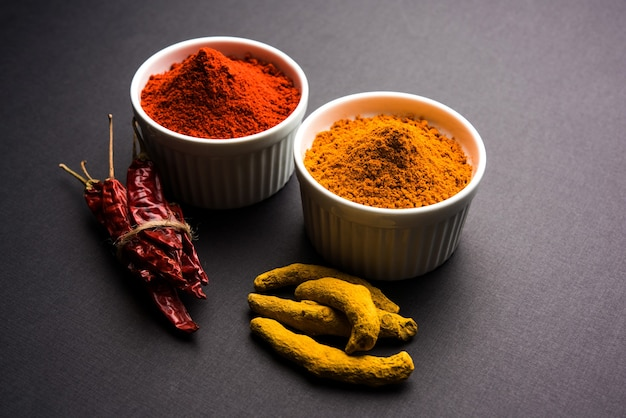 Куча куркумы или халди и порошка красного перца чили или мирчи в керамической миске на белой или черной поверхности