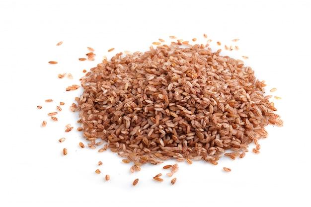 Куча неполированного коричневого риса изолированы. вид сбоку, крупным планом.