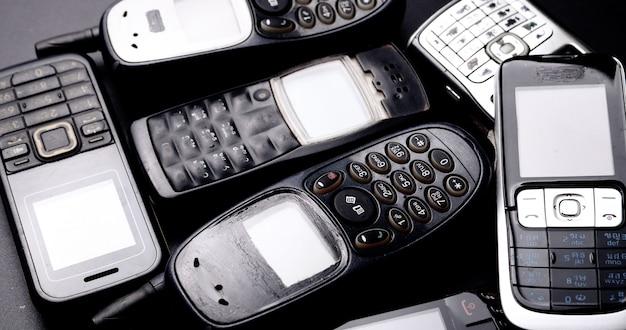 Куча старинных мобильных телефонов на черном фоне.