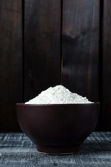 木製のテーブルの上のプレートに小麦粉のヒープ