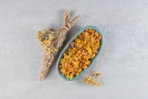 Куча желтого изюма в доске с сушеными цветами на каменном столе.
