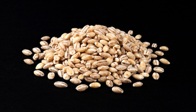 Heap of pearl barley grains isolated on black background, closeup