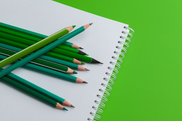 Heap of pencils on a bright green background