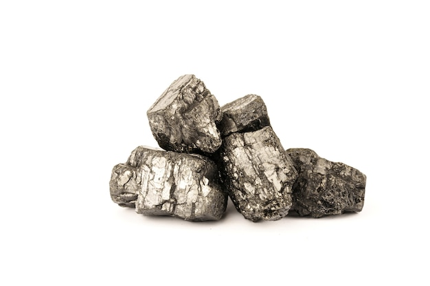 Heap of pieces of coal isolated on white wall.