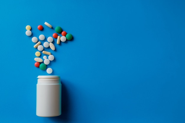 Heap of pills on blue  assorted pharmaceutical medicine pills, tablets and capsules and bottle on blue