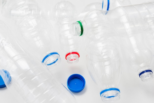 Heap of plastic bottles and caps on grey background