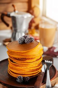 A heap of pumpkin pancakes with blackberries.