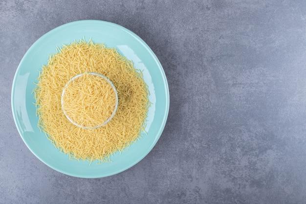 Heap of raw macaroni on blue plate.