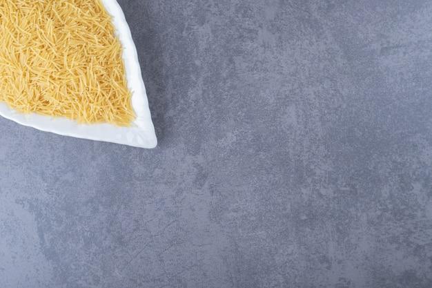 Heap of raw macaroni on leaf-shaped plate.