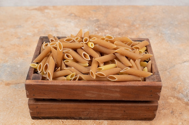 Mucchio di pasta cruda in un cesto di legno su sfondo marmo. foto di alta qualità