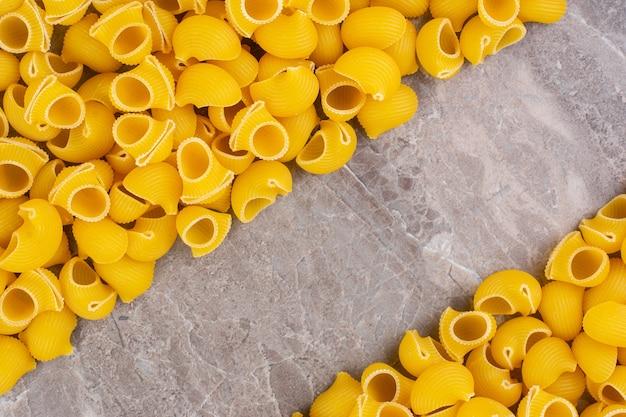 Mucchio di pasta da pipa cruda, sul marmo.