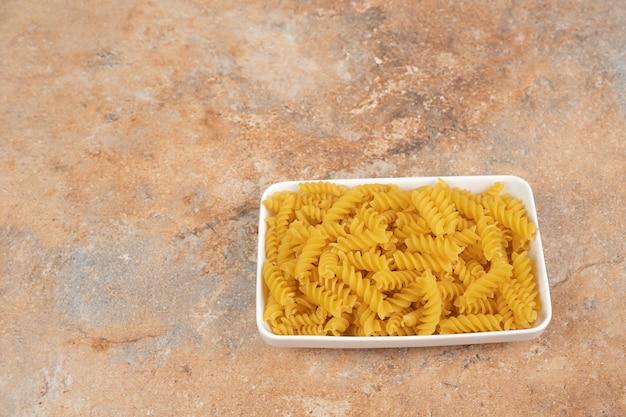 Mucchio di pasta a spirale cruda in un piatto bianco su sfondo di marmo