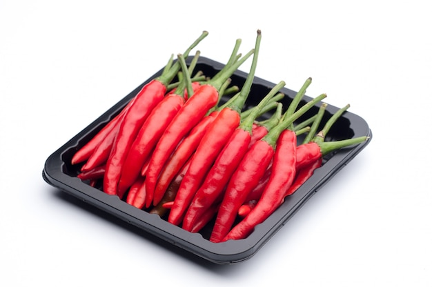 Heap of red hot chili pepper in black container on white background
