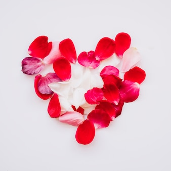 Heap of red petals in form of heart