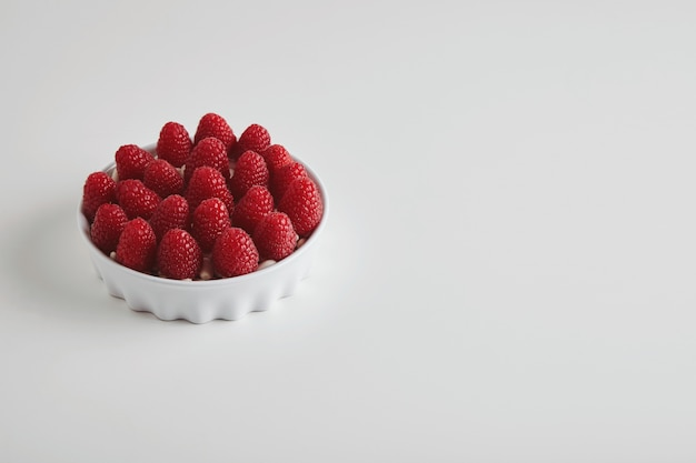 Heap of ripe raspberries accurately placed in ceramic bowl isolated on white table