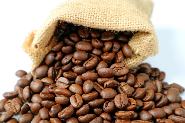 Heap of roasted coffee beans scattered from burlap bag