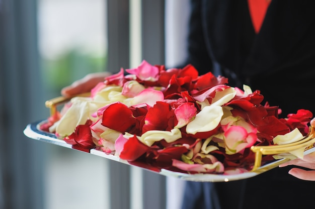 Heap rose petals on a silver tray