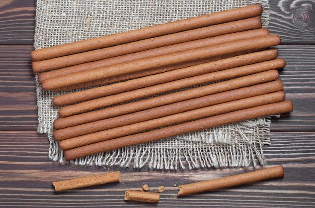 Heap of rye bread sticks on wooden background