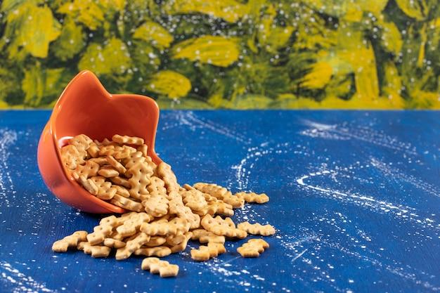 Mucchio di piccoli cracker salati disposti fuori dalla ciotola arancione.