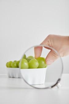 Cumulo di verde senza semi uva moscato antiossidante superfood organico nella ciotola di ceramica concetto per una sana alimentazione e nutrizione isolato sul tavolo bianco