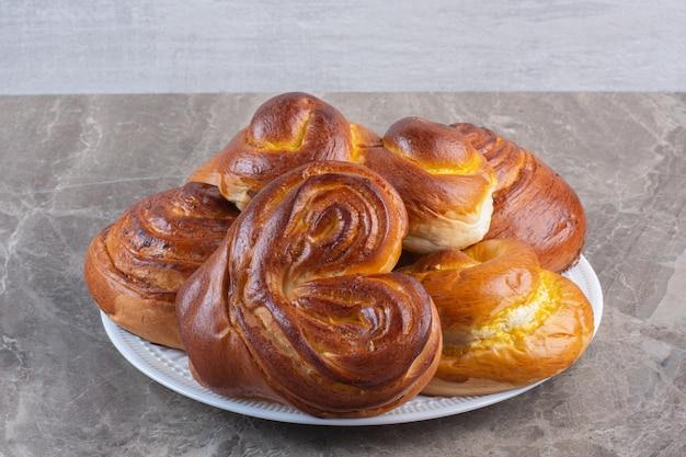 Cumulo di panini dolci su un piatto su sfondo marmo. foto di alta qualità