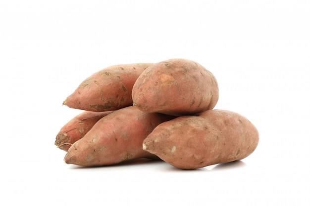 Heap of sweet potatoes isolated on white surface