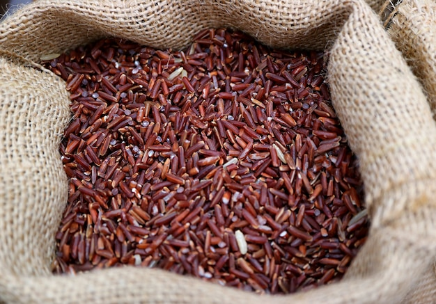 Heap of uncooked deep purple color rice-berry rice in a natural hemp sack
