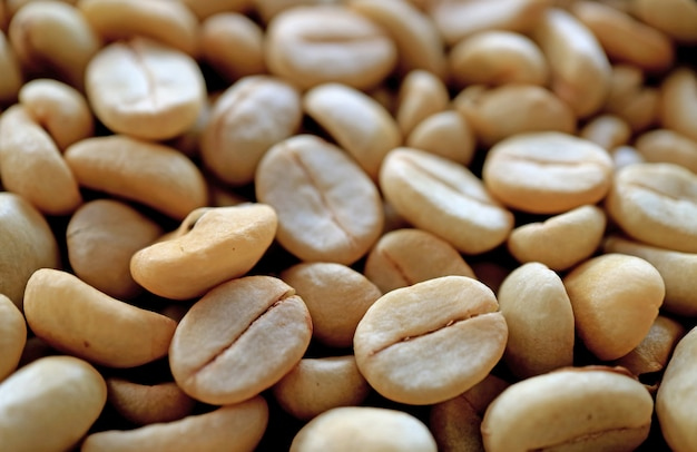 Heap of unroasted coffee beans with selective focus and blurred background