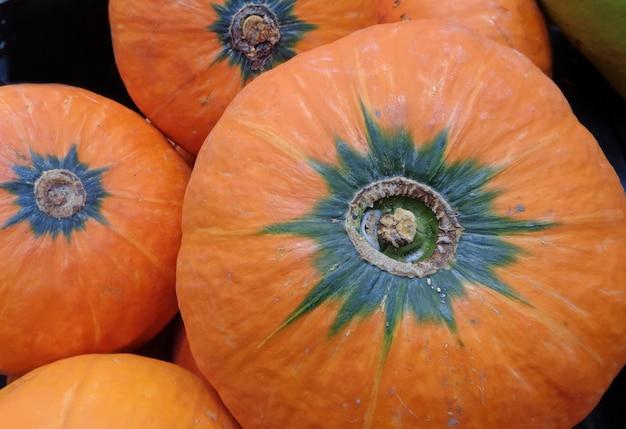 Heap of vibrant orange color ripe tropical pumpkins in market