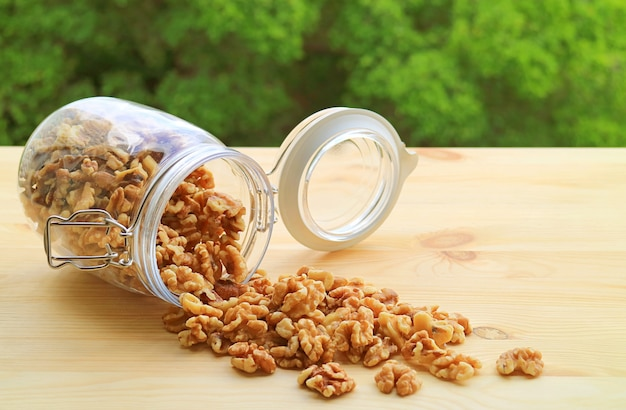 Heap of walnut kernels scattered from a glass jar onto the wooden table