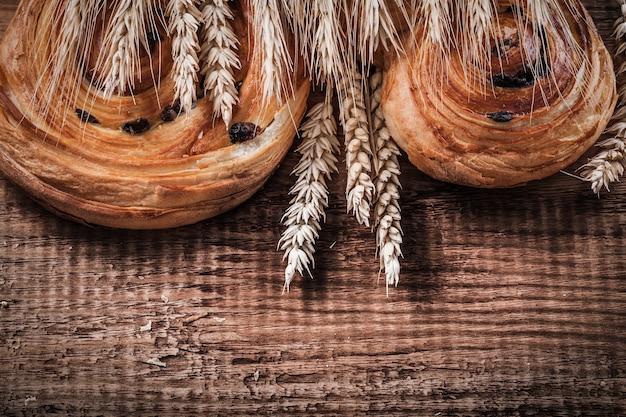 Heap of wheat ears sweet raisin bakery on oaken wooden board food and drink concept