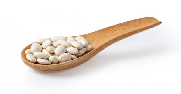 Heap of white beans in wood spoon on white wall