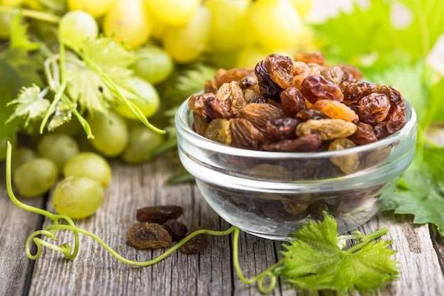 Heap of white raisins on wooden background and grape