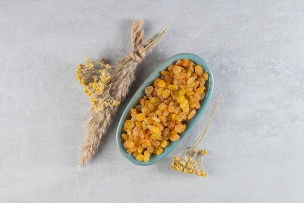 Heap of yellow raisins in board with dried flowers placed on stone table.