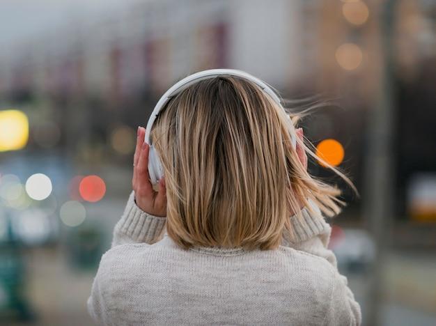 背後にある頭の形にheaphonesを保持している女性