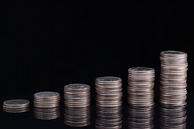 검은 배경에 오름차순으로 서있는 동전 더미