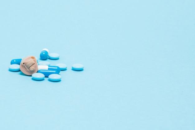 青い壁に補聴器と青い錠剤。医療、薬局、ヘルスケアの概念。