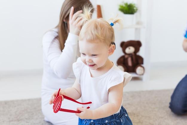 여자 아기의 귀에 보청기. 집에서 보청기를 착용하는 유아 아이. 장애 아동