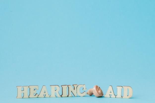 Слуховой аппарат на голубой стене. концепция медицины, фармации и здравоохранения. копировать пространство пустое место для текста или логотипа