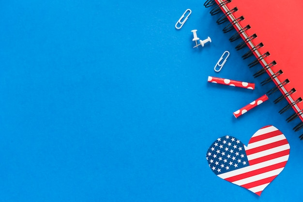 Heart in american flag color and stationery on blue surface
