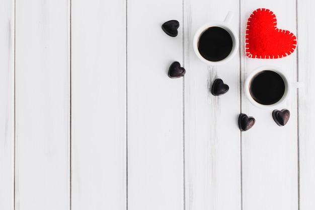 Сердце и конфеты возле кофейных чашек